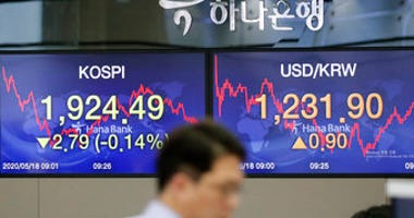 A currency trader walks near the screens showing the Korea Composite Stock Price Index (KOSPI), left, and the foreign exchange rate between U.S. dollar and South Korean won at the foreign exchange dealing room in Seoul, South Korea. (AP Photo/Lee Jin-man)