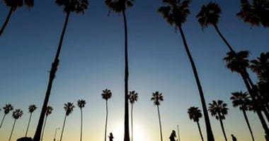 FILE - In this April 15, 2020, file photo, people keep their distance as they exercise outside of a closed La Jolla beach in San Diego. (AP Photo/Gregory Bull, File)