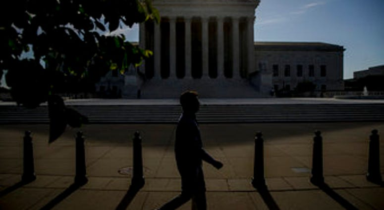 FILE - In this May 4, 2020, file a man walks past the Supreme Court in Washington. (AP Photo/Andrew Harnik, File)