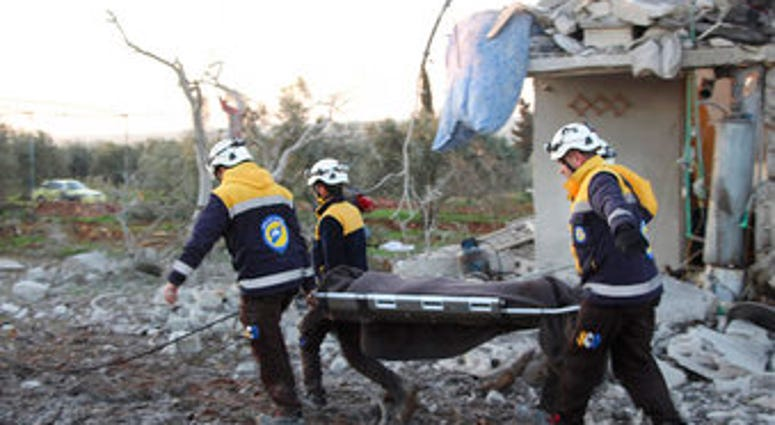 In this photo provided by the Syrian Civil Defense White Helmets, Syrian White Helmet civil defense workers carry a victim next to a destroyed house that was hit by Russian airstrike. (Syrian Civil Defense White Helmets via AP)