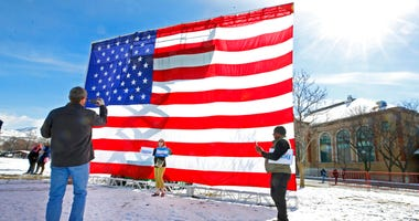 Supporters of Democratic presidential candidate Bernie Sanders take pictures in front of a large American flag before a rally Monday, March 2, 2020, in Salt Lake City. (AP Photo/George Frey)