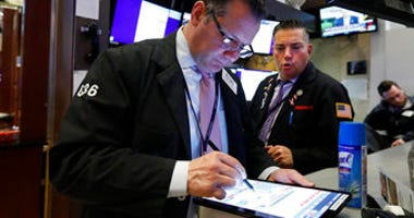 Traders Edward Curran, left, and Jonathan Mueller work on the floor of the New York Stock Exchange, Thursday, March 12, 2020. (AP Photo/Richard Drew)