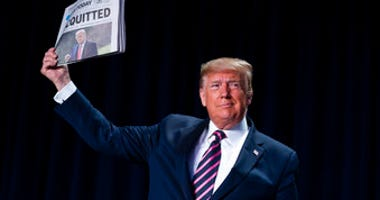 "President Donald Trump holds up a newspaper with a headline that reads ""ACQUITTED"" during the 68th annual National Prayer Breakfast, at the Washington Hilton, Thursday, Feb. 6, 2020, in Washington. (AP Photo/ Evan Vucci)"
