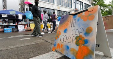"People walk near what is being called the ""No Cop Co-op"" were protesters and others can get free food and other supplies, Thursday, June 11, 2020, inside what is being called the ""Capitol Hill Autonomous Zone"" in Seattle.  (AP Photo/Ted S. Warren)"