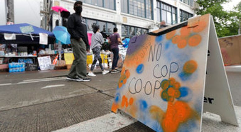 """People walk near what is being called the """"No Cop Co-op"""" were protesters and others can get free food and other supplies, Thursday, June 11, 2020, inside what is being called the """"Capitol Hill Autonomous Zone"""" in Seattle.  (AP Photo/Ted S. Warren)"""