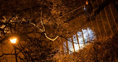 A New York City police department detective use a flashlight to look for evidence in Morningside Park, Thursday, Dec. 12, 2019, in the Upper West Side of Manhattan.  (AP Photo/Mary Altaffer)