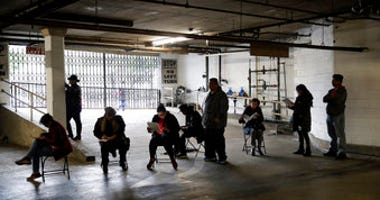 Unionized hospitality workers wait in line in a basement garage to apply for unemployment benefits at the Hospitality Training Academy Friday, March 13, 2020, in Los Angeles. (AP Photo/Marcio Jose Sanchez)