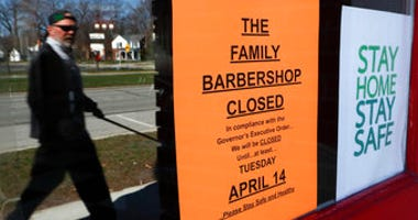 A pedestrian walks by The Family Barbershop, closed due to a Gov. Gretchen Whitmer executive order, in Grosse Pointe Woods, Mich., Thursday, April 2, 2020. (AP Photo/Paul Sancya)