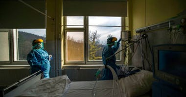 FILE - In this March 24 file photo, medical staff members check a ventilator in protective suits at the care unit for the new COVID-19 infected patients inside the Koranyi National Institute of Pulmonology in Budapest. (Zoltan Balogh/MTI via AP, File)