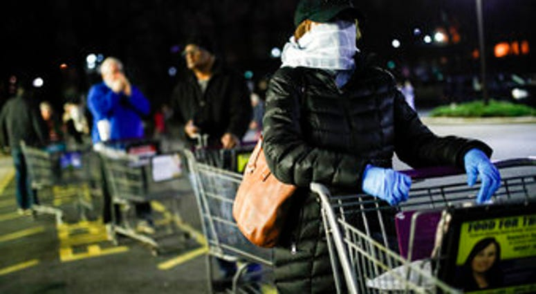 Customers wearing protective masks and gloves wait in line at a Stop & Shop supermarket that opened special morning hours to serve people 60-years and older due to coronavirus concerns. (AP Photo/John Minchillo)