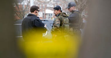 Law enforcement personnel work at the scene of a shooting, Wednesday, Feb. 12, 2020, in Baltimore. Two law enforcement officers with a fugitive task force were injured and a suspect died in the shooting. (Ulysses Muñoz/The Baltimore Sun via AP)