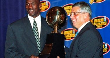 FILE - In this June 18, 1996, file photo, Chicago Bulls' Michael Jordan, left, receives the NBA Finals Most Valuable Player trophy from Commissioner David Stern during a ceremony in Chicago. (AP Photo/Charles Bennett, File)