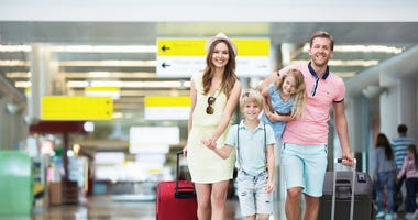 Happy family with suitcases in the airport. © Denis Raev | Dreamstime.com