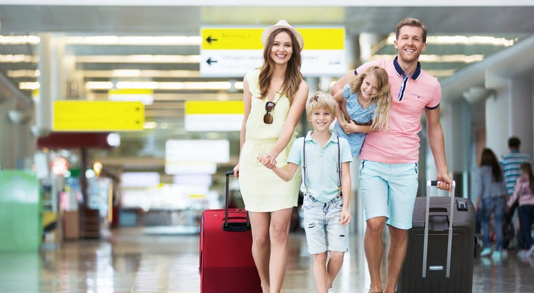 Happy family with suitcases in the airport. © Denis Raev   Dreamstime.com