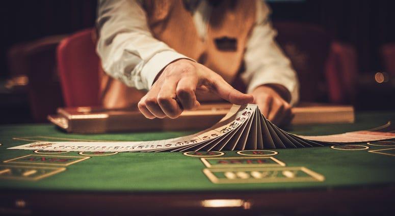 Croupier behind gambling table in a casino. (Dreamstime)