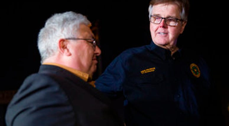 Lt. Gov. Dan Patrick, right, puts his hand on West Freeway Church of Christ senior preaching minister Britt Farmer after speaking at a news conference following a fatal shooting at his church. (Juan Figueroa/The Dallas Morning News via AP)