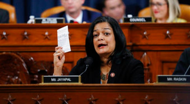 Rep. Pramila Jayapal, D-Wash., holds up a copy of the U.S. Constitution as she votes on the articles of impeachment against President Donald Trump, Friday, Dec. 13, 2019, in the House Judiciary Committee on Capitol Hill. (AP Photo/Andrew Harnik)