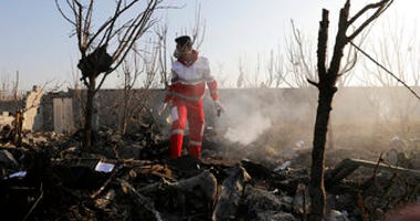 A rescue worker searches the scene where an Ukrainian plane crashed in Shahedshahr, southwest of the capital Tehran, Iran, Wednesday, Jan. 8, 2020. (AP Photo/Ebrahim Noroozi)