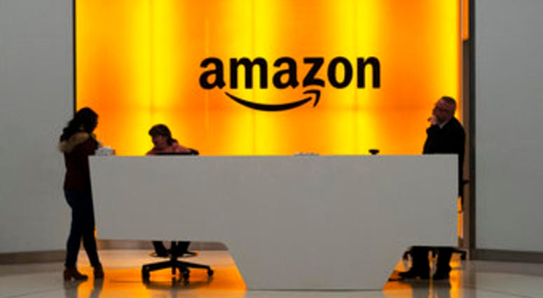 "FILE - In this Feb. 14 file photo people stand in the lobby for Amazon offices in New York. Amazon says President Trump's ""improper pressure"" harmed its chances of winning a $10 billion Pentagon contract. (AP Photo/Mark Lennihan, File)"
