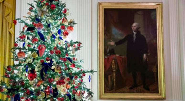 A decorated tree stands next to the portrait of President George Washington in the East Room during the 2019 Christmas preview at the White House, Monday, Dec. 2, 2019, in Washington. (AP Photo/Alex Brandon)