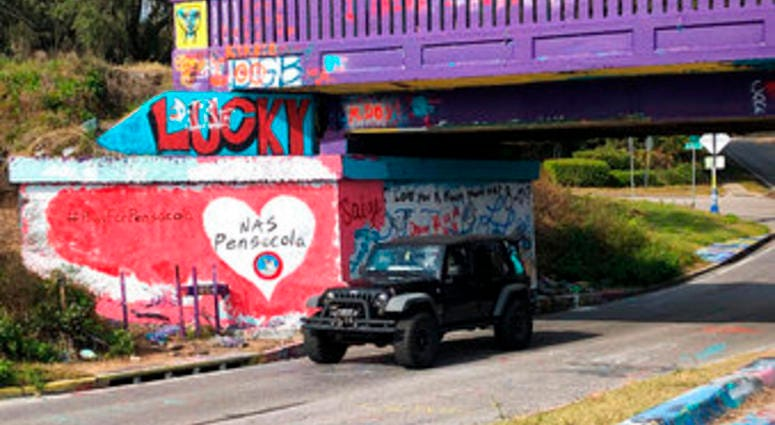A vehicle drives by a tribute to victims of the Naval Air Station Pensacola that was freshly painted on what's known as Graffiti Bridge in downtown Pensacola, Fla., on Saturday, Dec. 7, 2019.  (AP Photo/Brendan Farrington)