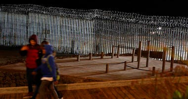 Floodlights from the U.S, illuminate the border wall, topped with razor wire, as a people pass Monday, Jan. 7, 2019, at the beach in Tijuana, Mexico. (AP Photo/Gregory Bull)