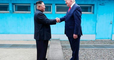 In this Sunday, June 30, 2019, photo provided by the North Korean government, North Korean leader Kim Jong Un, left, and U.S. President Donald Trump shake hands over the military demarcation line. (Korean Central News Agency/Korea News Service via AP)