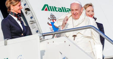 Pope Francis is greeted by a flight attendant as he boards his flight to Maputo, Mozambique, in Rome's Fiumicino International airport, Wednesday, Sept. 4, 2019.  (AP Photo/Andrew Medichini)