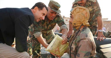 In this photo released on the official Facebook page of the Syrian Presidency, Syrian President Bashar Assad, left, speaks with Syrian troops during his visit to the strategic town of Habeet, in the northwestern province of Idlib, Syria. (Facebook page of