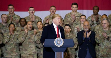 President Donald Trump, center, with Afghan President Ashraf Ghani, second from the right, and Joint Chiefs Chairman Gen. Mark Milley, right, while addressing members of the military during a surprise Thanksgiving Day visit, Thursday, Nov. 28, 2019, at Ba