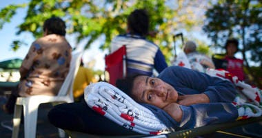 58 years-old Maribel Rivera Silva rests outside a shelter afraid of aftershocks, after an earthquake in Guanica, Puerto Rico, Tuesday, Jan. 7, 2020. (AP Photo/Carlos Giusti)