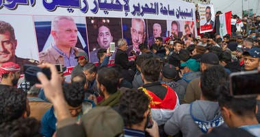 """Anti government Iraqi protesters gather by a banner with pictures of Iraqi politicians and Arabic that reads """"the Tahrir square questionnaire to select a prime minister,"""" during the ongoing protests in Tahrir square, Baghdad, Iraq, Friday, Jan. 10, 2020."""