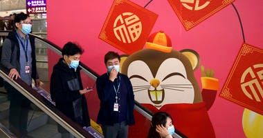 People wear face masks as they ride an escalator at the Hong Kong International Airport in Hong Kong, Tuesday, Jan. 21, 2020.  .(AP Photo/Ng Han Guan)
