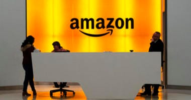 """FILE - In this Feb. 14 file photo people stand in the lobby for Amazon offices in New York. Amazon says President Trump's """"improper pressure"""" harmed its chances of winning a $10 billion Pentagon contract. (AP Photo/Mark Lennihan, File)"""