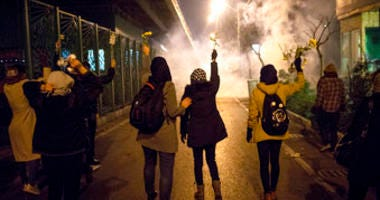 In this photograph taken Saturday, Jan. 11, protesters hold flowers as tear gas fired by police rises at a demonstration in front of Amir Kabir University in Tehran, to remember victims of a Ukrainian airplane shot down by an Iranian missile. (AP Photo)