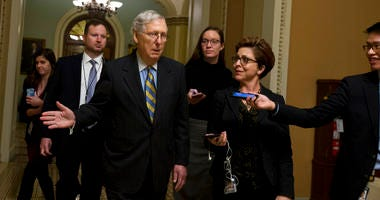 Senate Majority Leader Mitch McConnell, R-Ky., talks to reporters as leaves the senate chamber on Capitol Hill in Washington, Wednesday, Dec.18, 2019. (AP Photo/Jose Luis Magana)