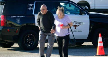 An elderly couple walks from West Freeway Church of Christ hours after a fatal shooting at the church, Sunday, Dec. 29, 2019, in White Settlement, Texas. The couple declined to comment to reporters. (AP Photo/David Kent)