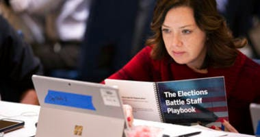 In this Monday, Dec. 16, 2019, photo, Mandy Vigil, from New Mexico, works during an exercise run by military and national security officials, for state and local election officials to simulate different scenarios for elections.  (AP Photo/Alex Brandon)