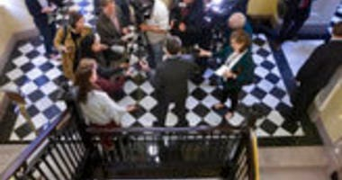 Virginia Gov. Ralph Northam, center back to camera, talks to the media after he outlined his legislative agenda at the Capitol in Richmond, Va., Tuesday, Jan. 7, 2020. (AP Photo/Steve Helber)