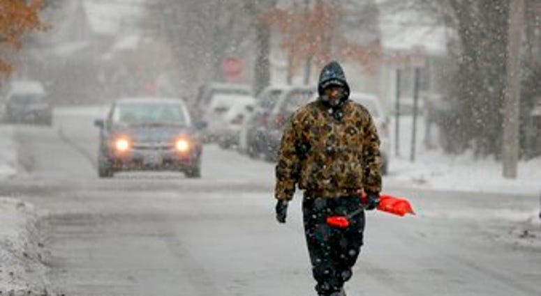 Bill Parham walks down an icy street in Maplewood, Mo., looking to clear snow off people's driveways and sidewalks on Monday, Dec. 16, 2019. (David Carson/St. Louis Post-Dispatch via AP)