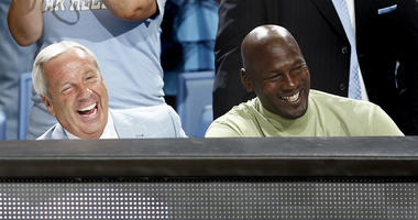 Roy Williams and Michael Jordan watch a game.
