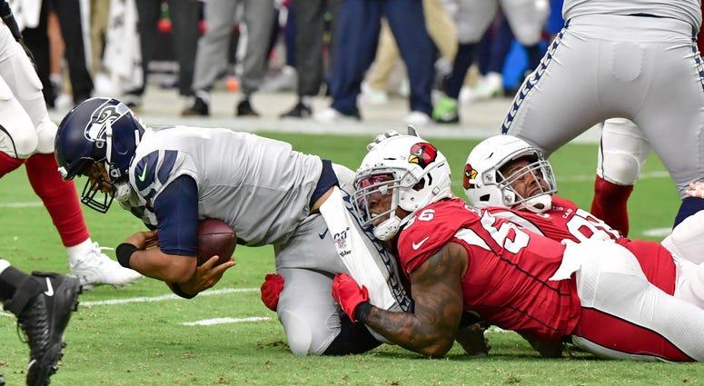 Sep 29, 2019; Glendale, AZ, USA; Arizona Cardinals outside linebacker Terrell Suggs (56) sacks Seattle Seahawks quarterback Russell Wilson (3) in the first half at State Farm Stadium. Mandatory Credit: Matt Kartozian-USA TODAY Sports