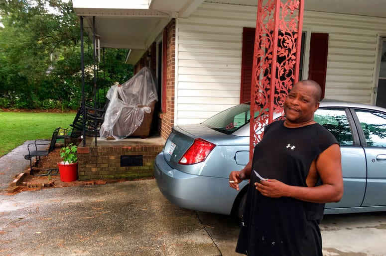 James Howell Jr. sizes up how to protect his home Tuesday, Sept. 11, 2018, in Princeville, N. C., from the approaching Hurricane Florence. The house was damaged by Hurricane Matthew in 2016. Howell said the furniture on his porch is there because he had t
