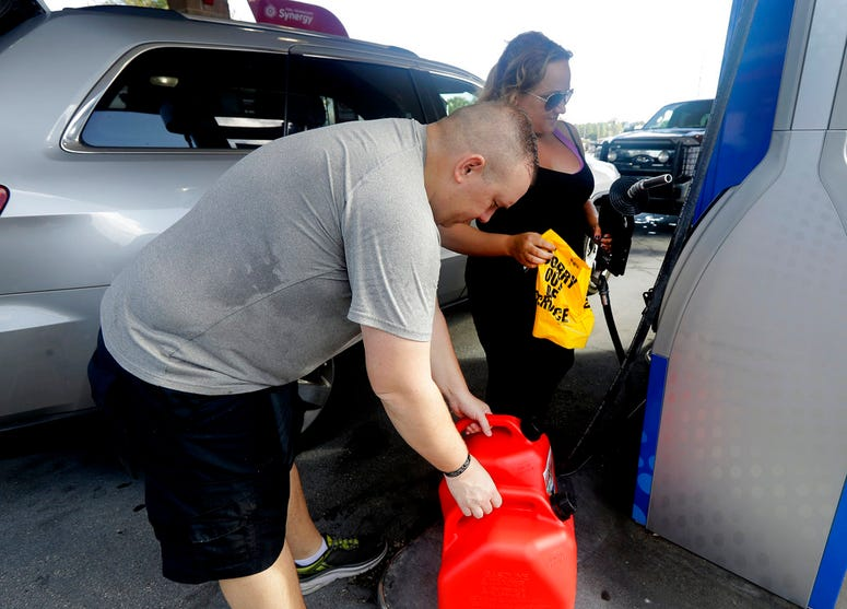 "Sarah Dankanich, right, removes an ""out of service"" wrapper from a gas pump as her husband, Bryan Dankanich, left, prepares to pump gas in cans in advance of Hurricane Florence in Wilmington, N.C., Wednesday, Sept. 12, 2018. Florence exploded into a poten"