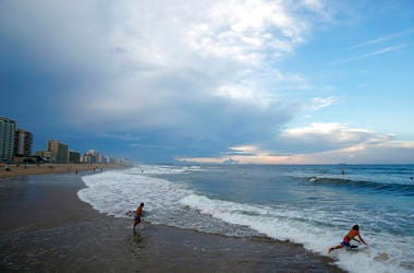 Surfers head to the waves, Tuesday, Sept. 11, 2018, in Virginia Beach, Va., before the arrival of Hurricane Florence