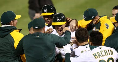 Oakland A's players mob teammate Matt Olson after his walk-off grand slam to beat the Angels on Opening Day