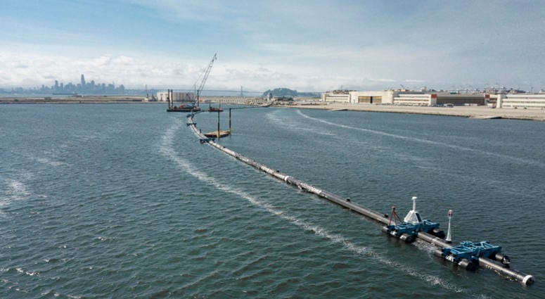 In this Monday, Aug. 27, 2018 photo provided by The Ocean Cleanup, a long floating boom that will be used to corral plastic litter in the Pacific Ocean is assembled in Alameda, Calif. Engineers will deploy a trash collection device to corral plastic litte