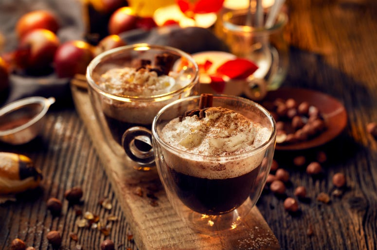 Hot chocolate with whipped cream, sprinkled with aromatic cinnamon in glass cups. Snack, brown.