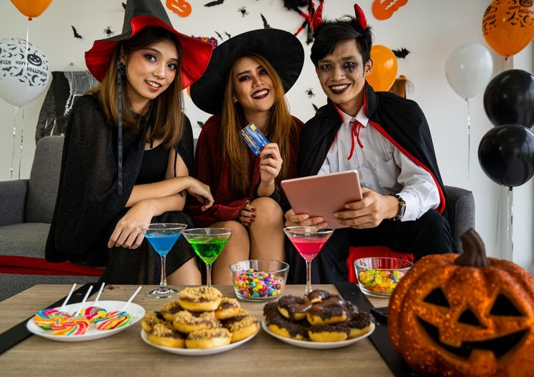 Group of people celebrating a Halloween party in costumes