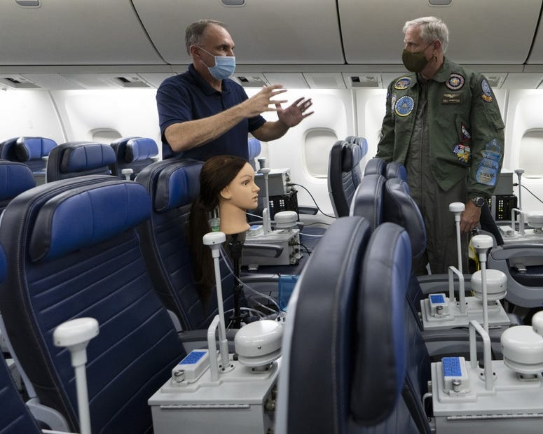Vice Adm. Dee Mewbourne (right), deputy commander, U.S. Transportation Command, receives a description of the airflow particle test from David Silcott (left), chief executive of S3i, a biological research company, on board a United Airlines 767 aircraft.